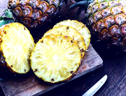 Slices of whole pineapple on a cutting board