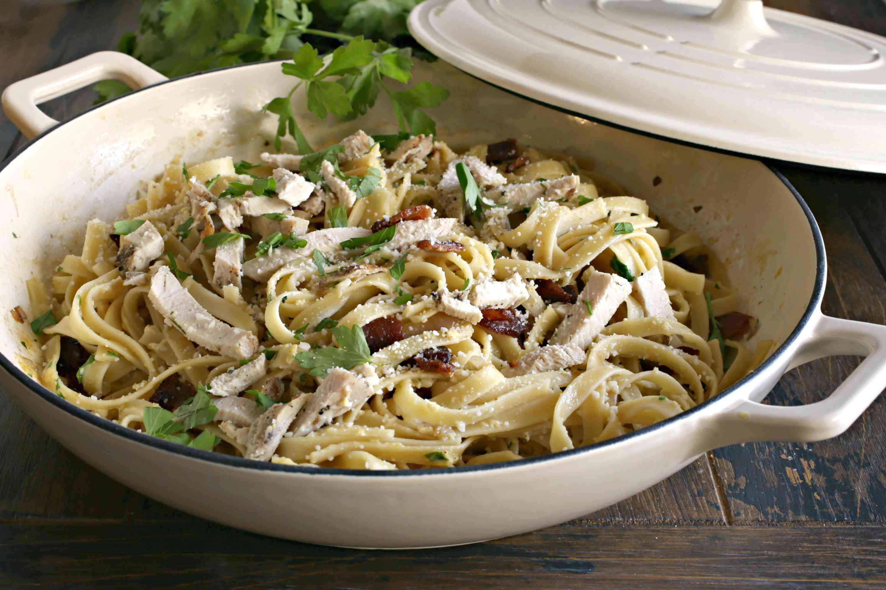 Chicken carbonara in a serving bowl with parsley garnish