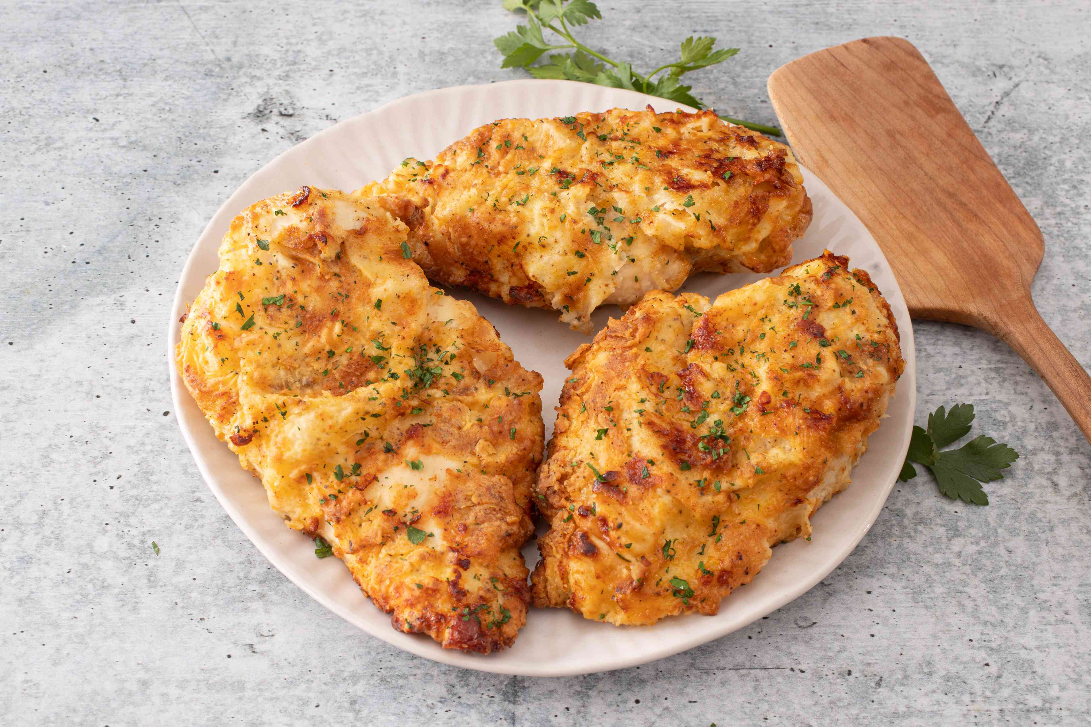 Air fryer chicken breasts, fried, on a plate garnished with parsley
