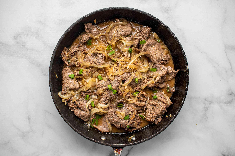 Garlicky Filipino Bistek (Bistek Tagalog) in a frying pan