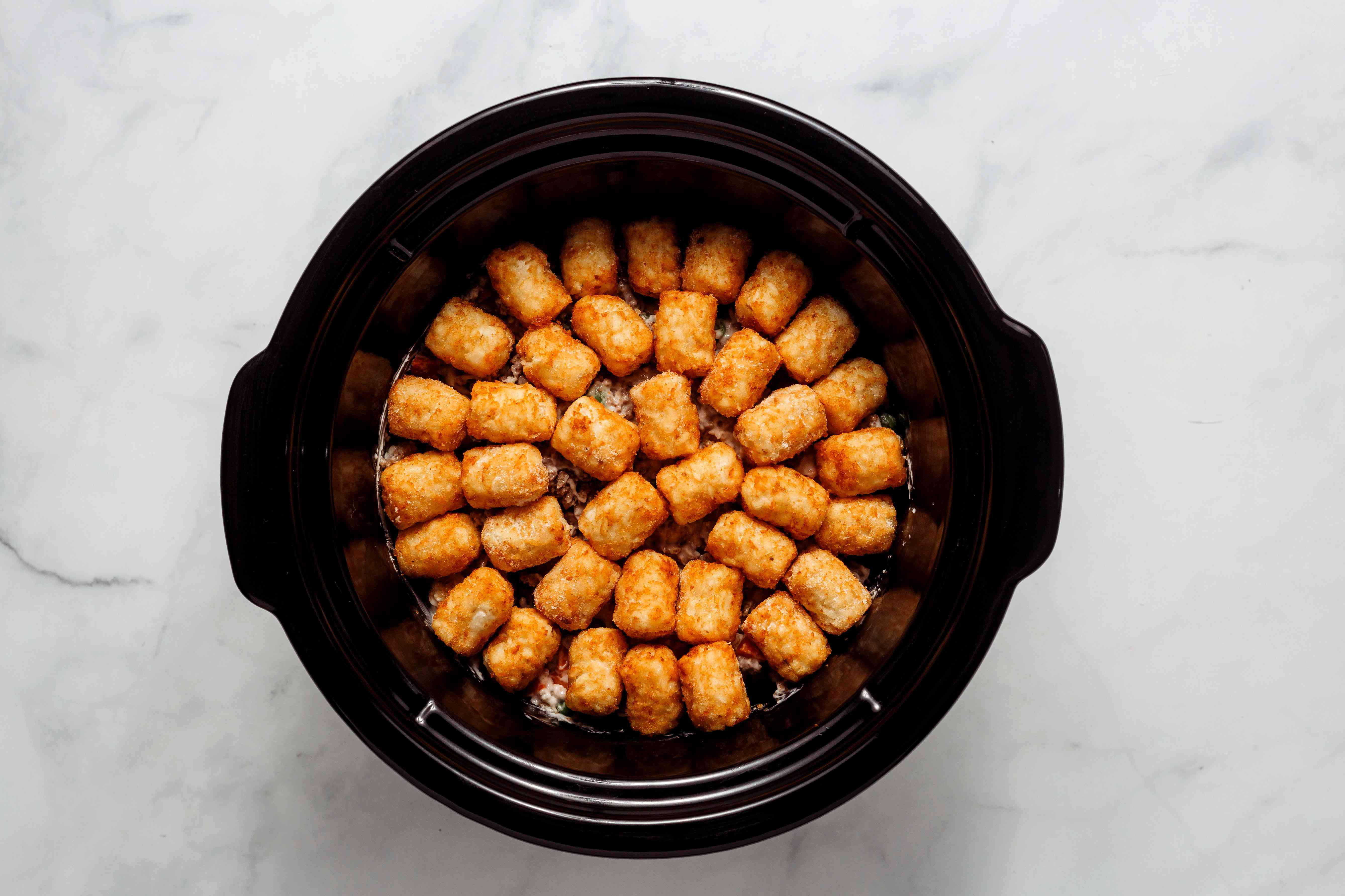tater tots on top of the casserole mixture in a slow cooker
