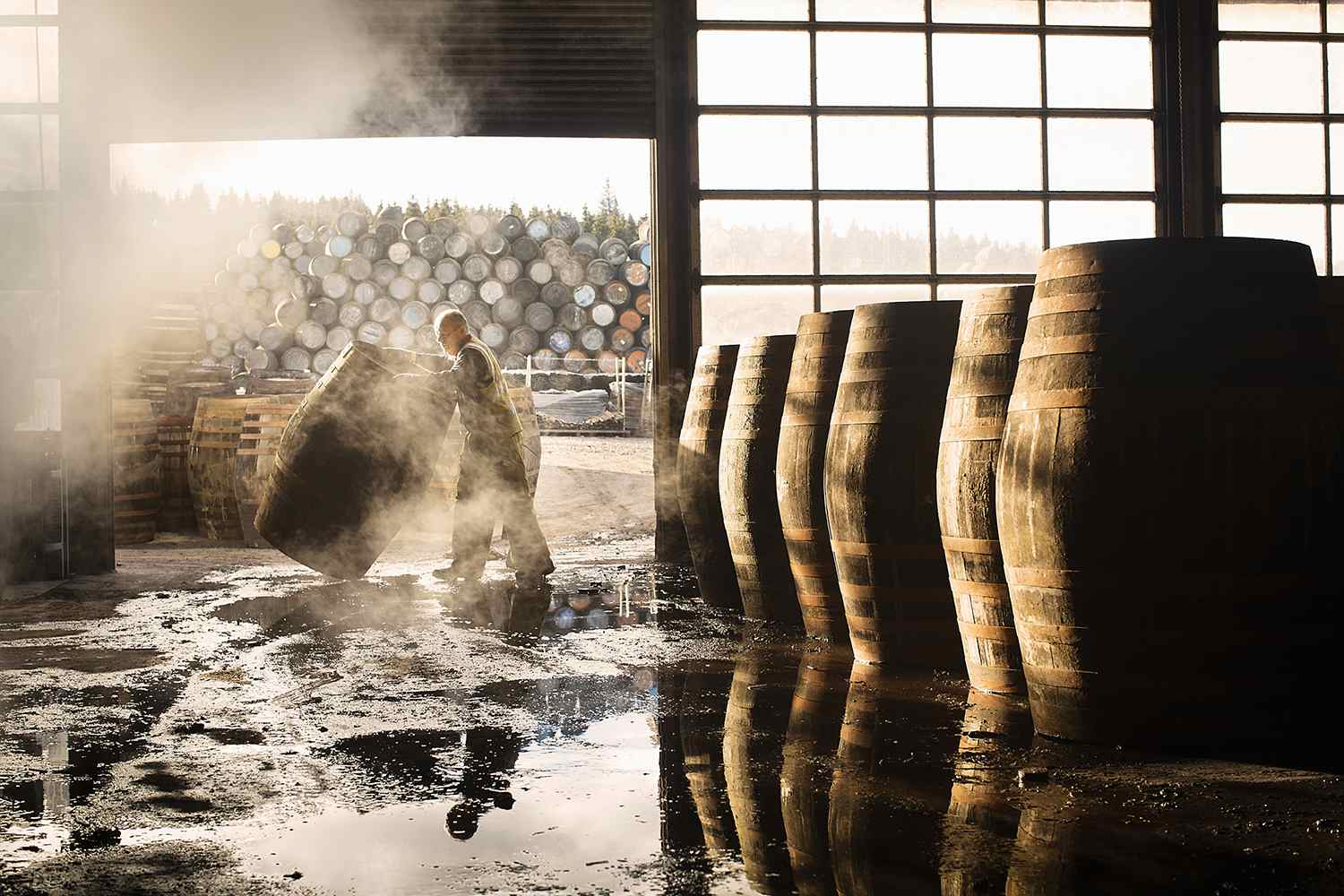A cooper works at a whiskey barrel cooperage.