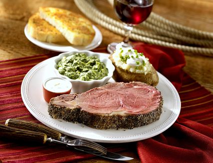 Prime rib with baked potato and creamed spinach on a plate