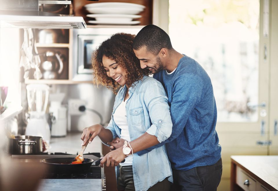 young couple cooking over stovetop