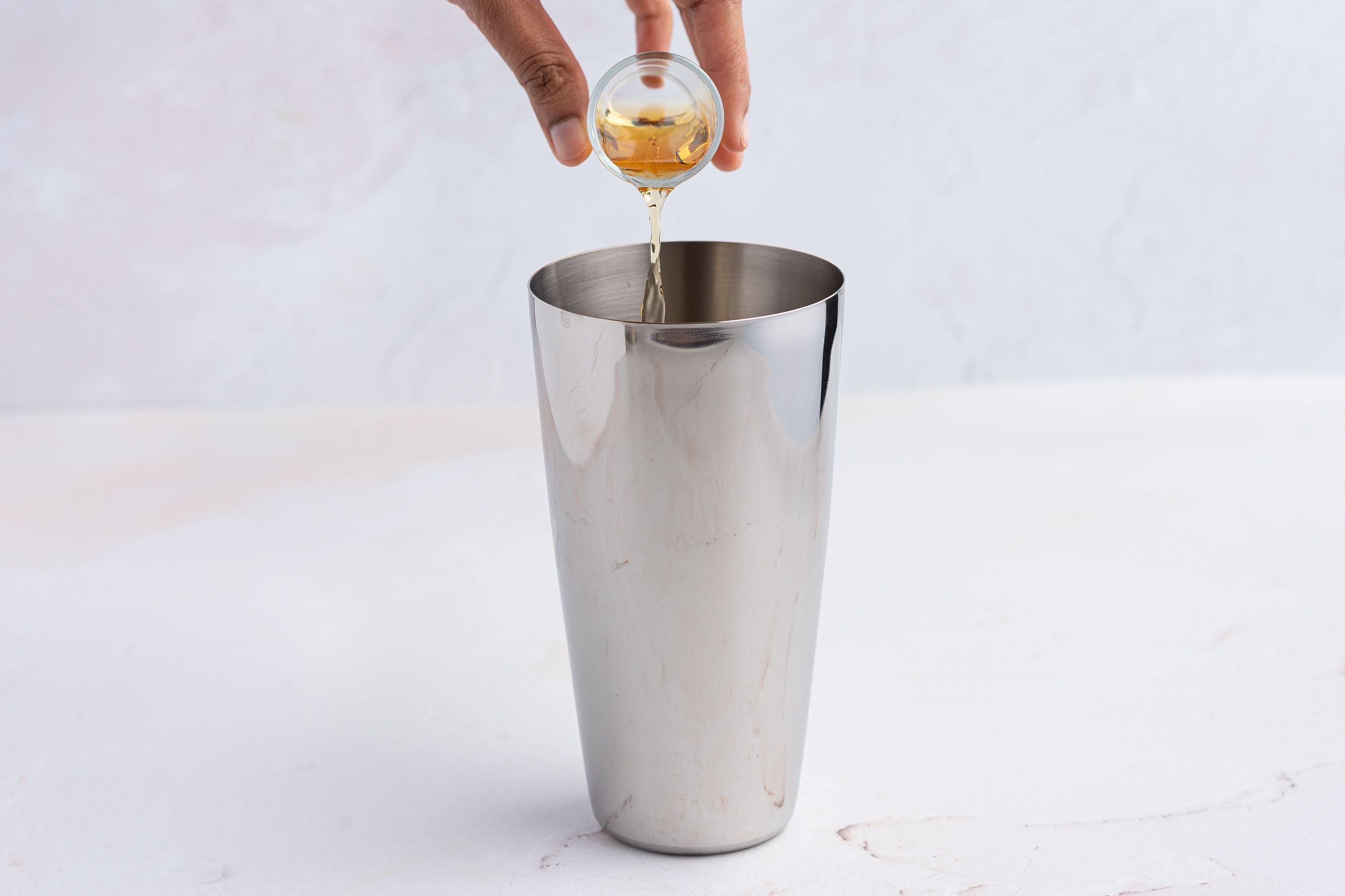 Whiskey, triple sec, sugar, and bitters in a cocktail shaker
