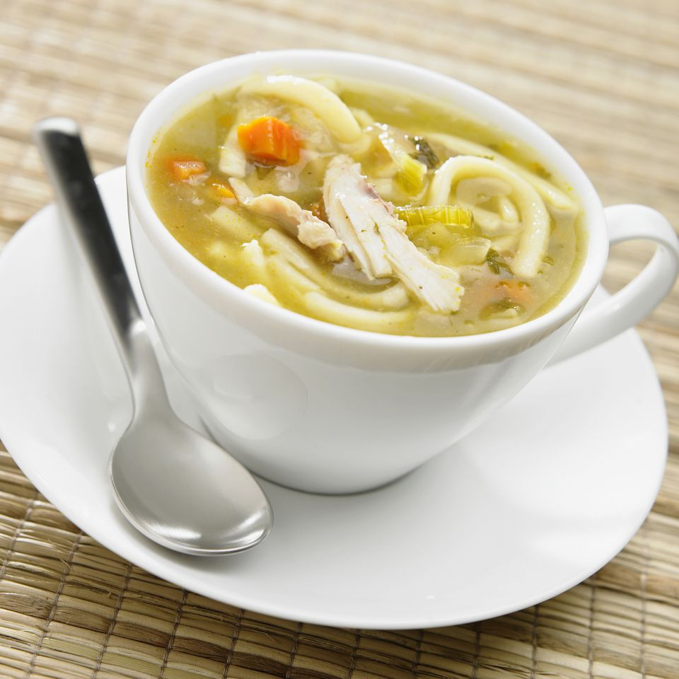 Chicken noodle soup in a cup on a saucer