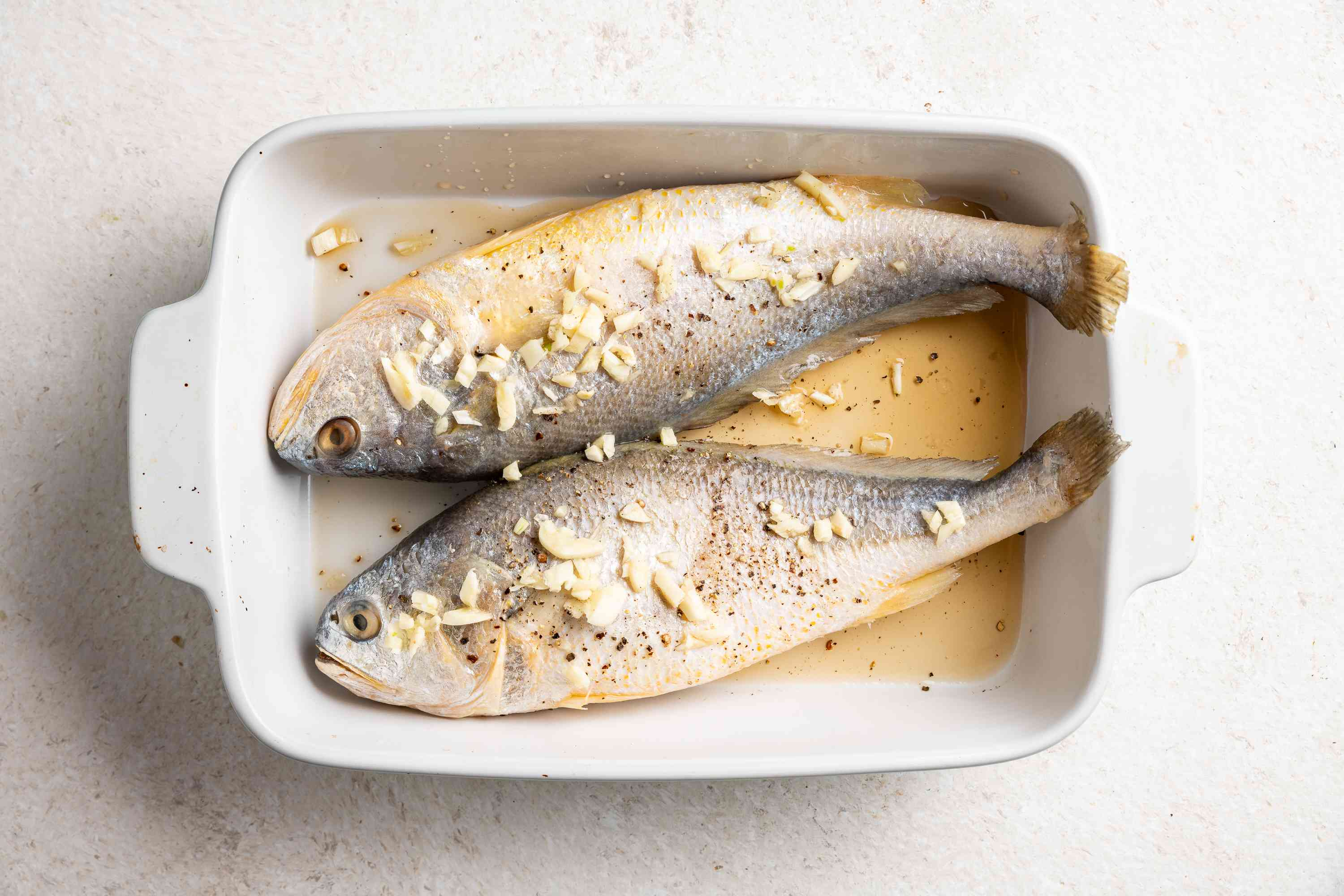 whole fish with seasoning in a dish