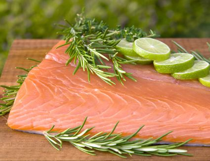 Fresh wild King salmon fish fillet, rosemary and lime on cedar plank