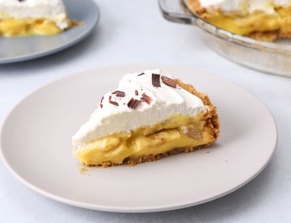 A slice of banana pudding pie topped with whipped cream