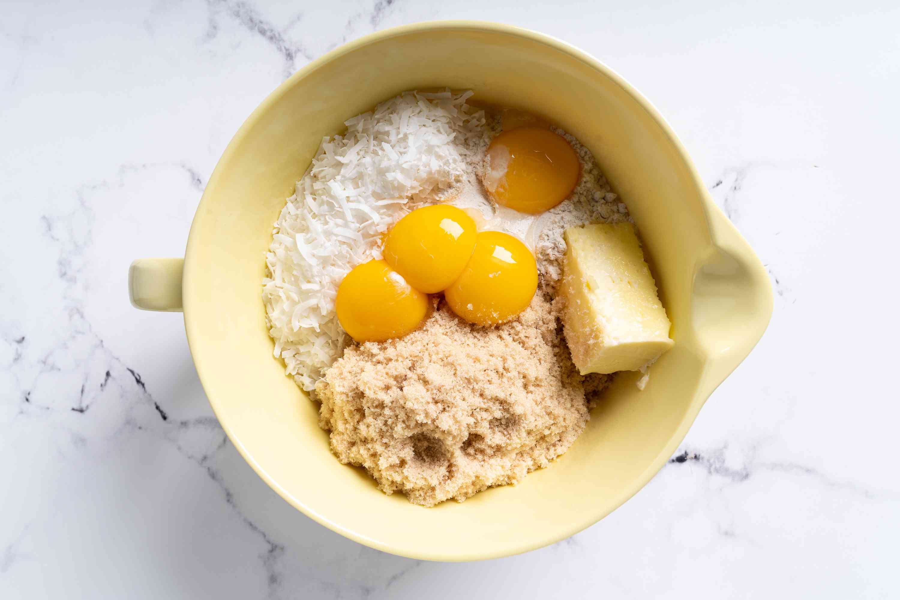 mix coconut flakes, flour, egg yolks, brown sugar, butter and extract together in a bowl
