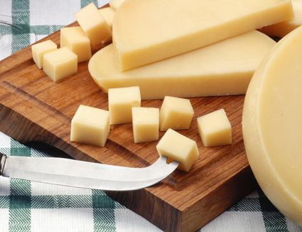 Provolone cheese on a wooden cutting board with a knife