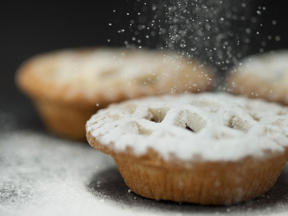 Icing being sprinkled over Christmas mince pies