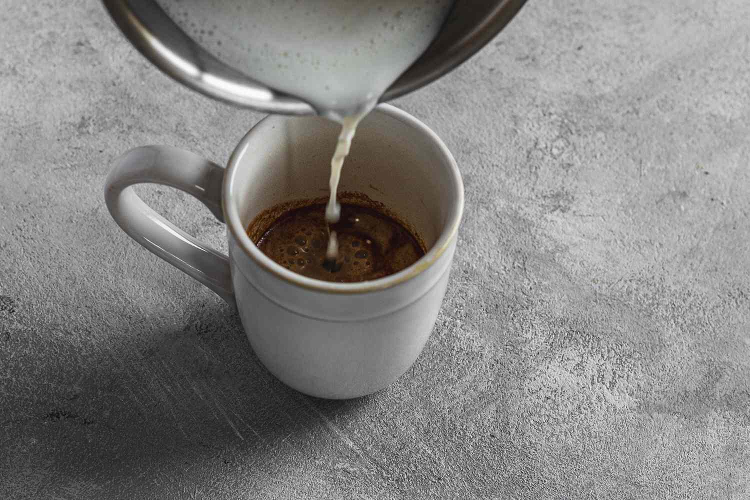 milk poured over coffee mix in a cup