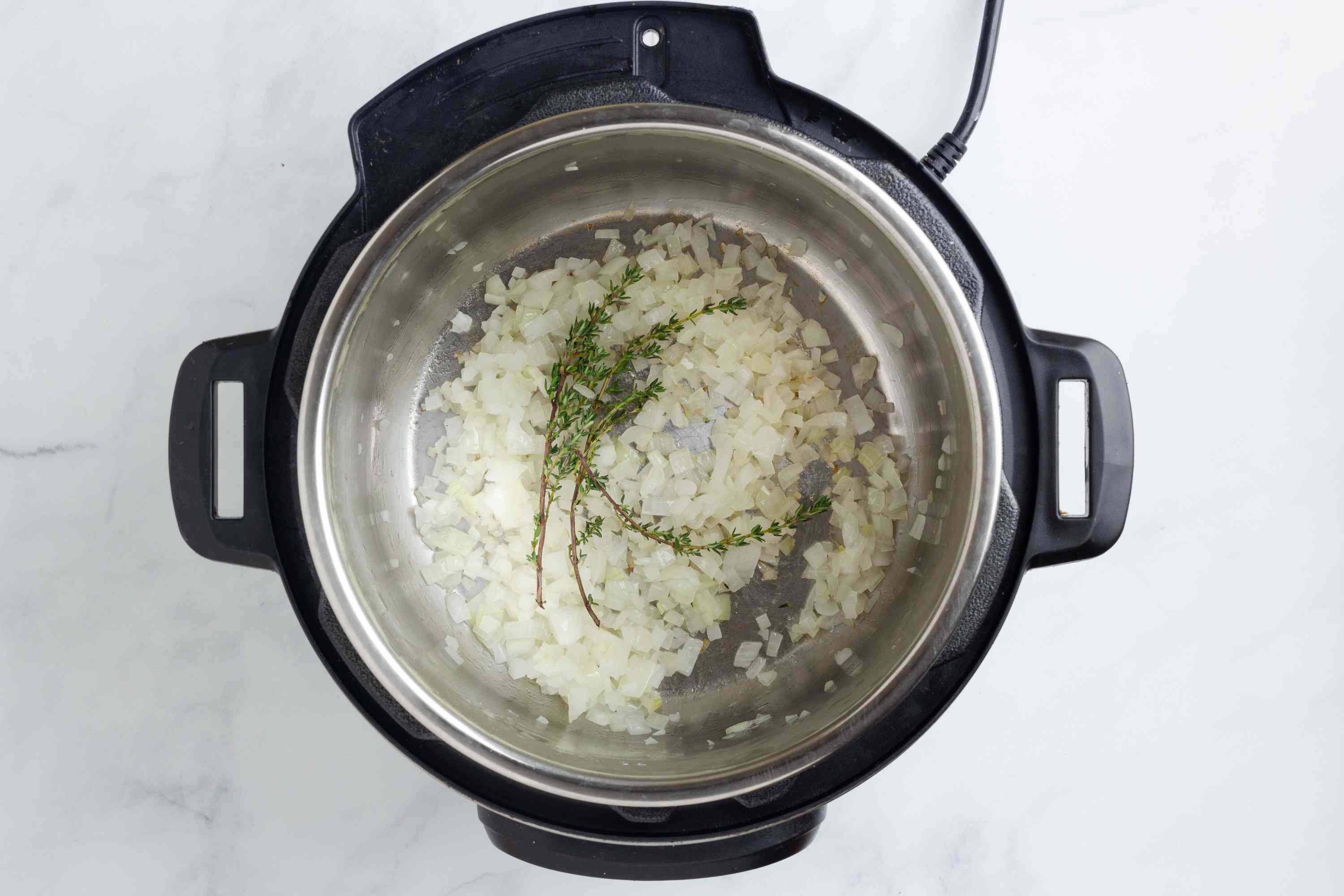 onions and herbs in a pressure cooker