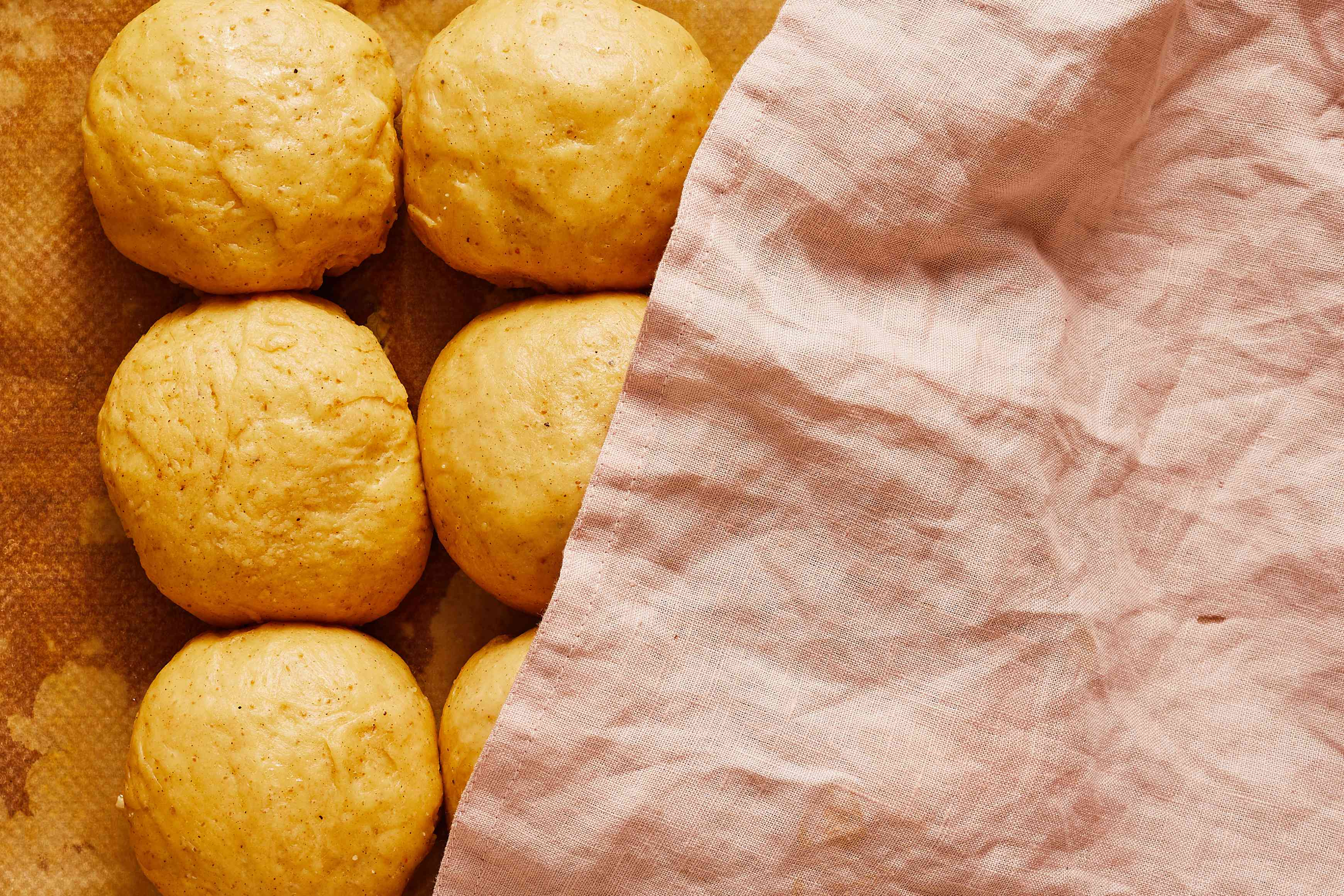 dough balls risen, with kitchen towel covering them partly