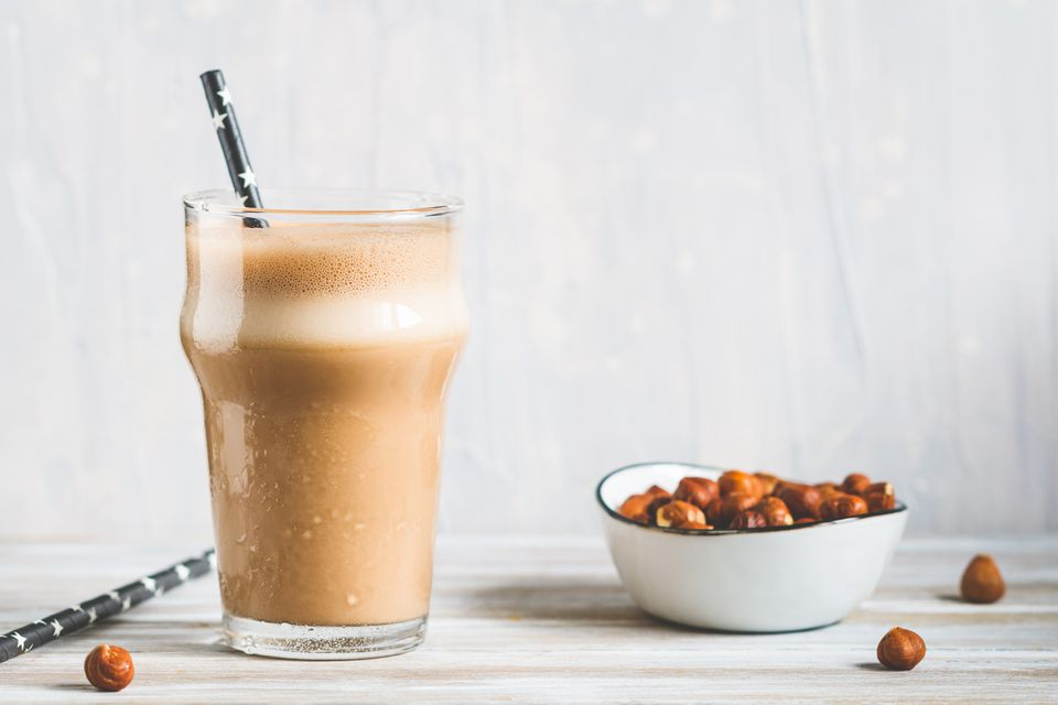 Peanut butter chocolate protein shake in a glass with a straw and a bowl of nuts