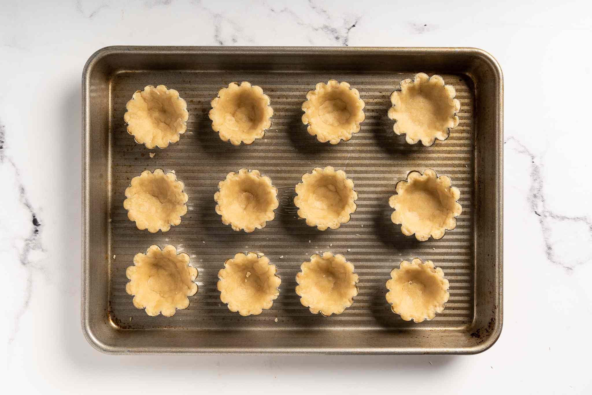 Tart molds lined with egg tart pastry on a small baking sheet