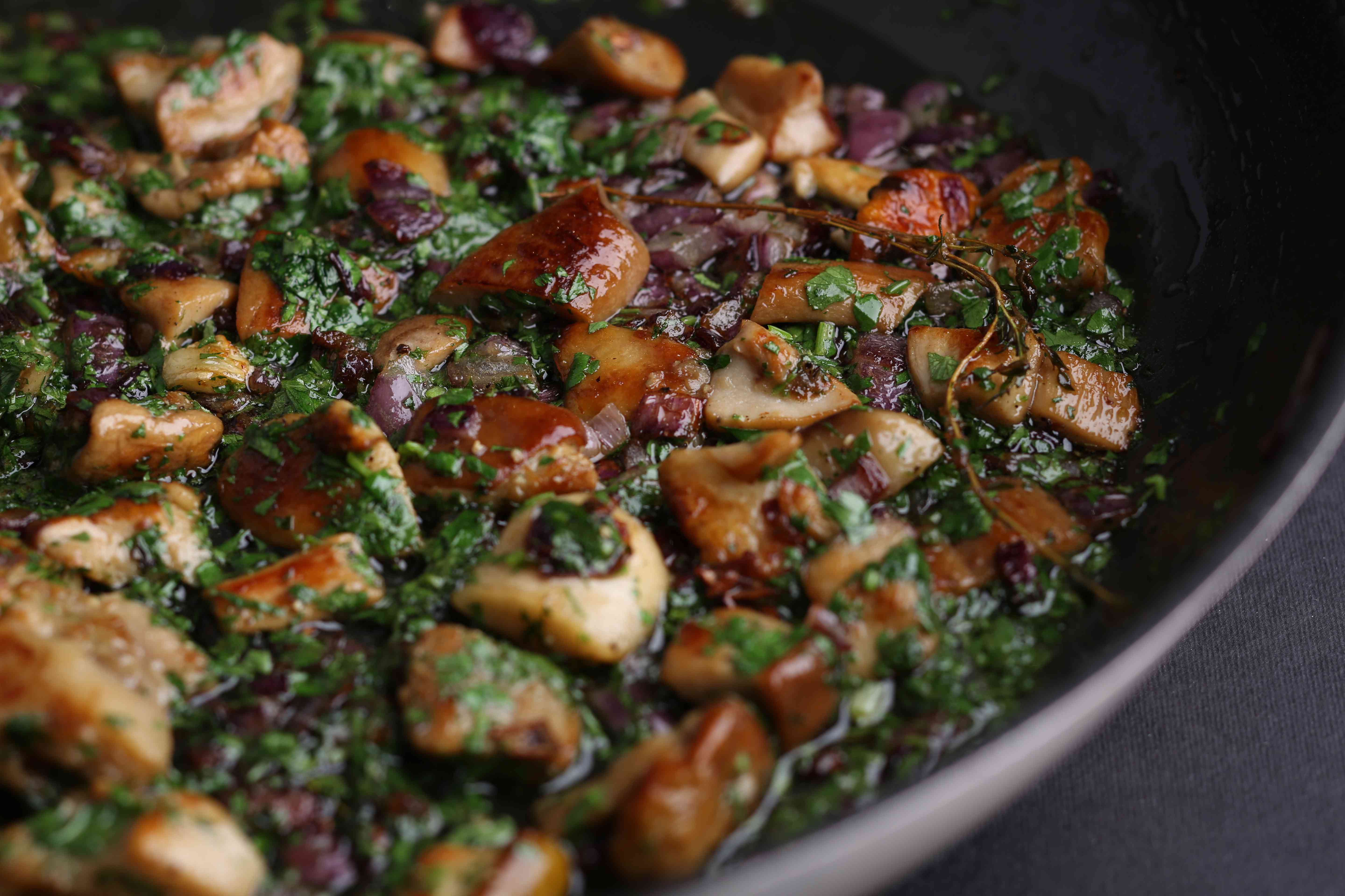 Fried mushrooms with onions and greens in a skillet on
