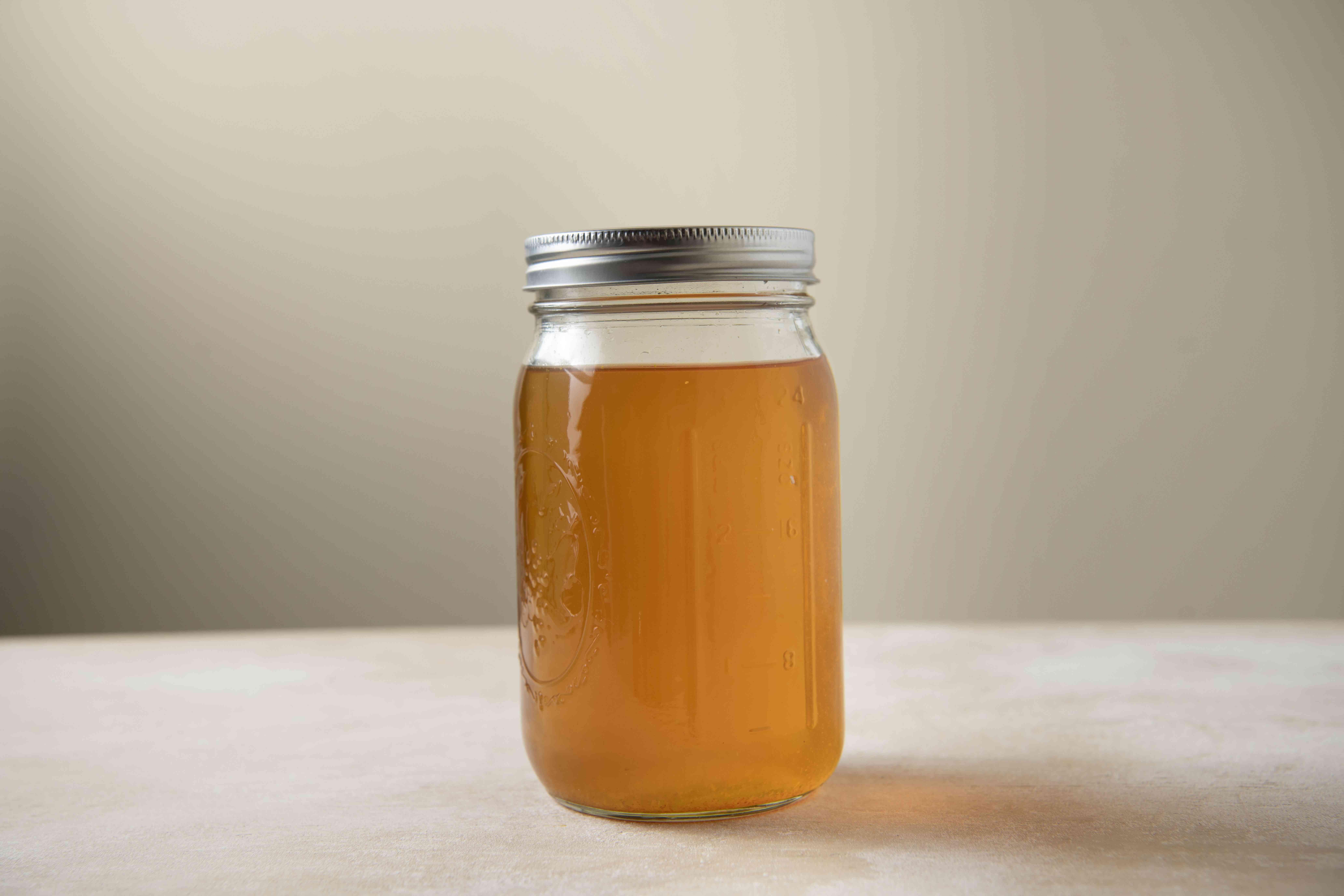 A jar of peach liqueur in a dark setting