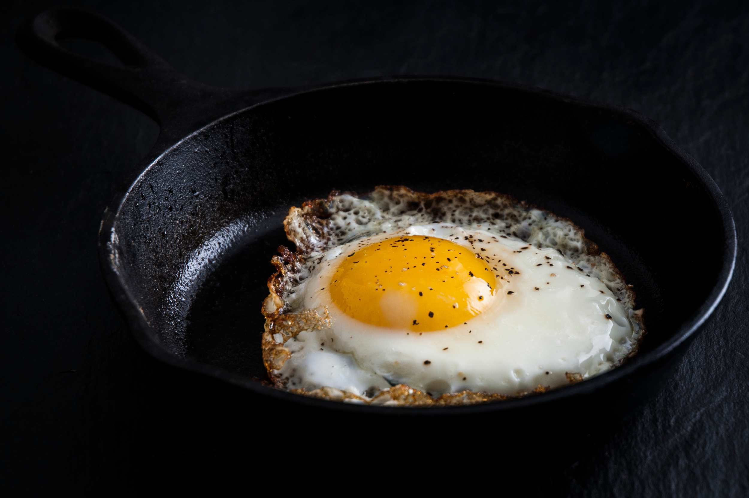 Fried egg cooking in cast iron skillet