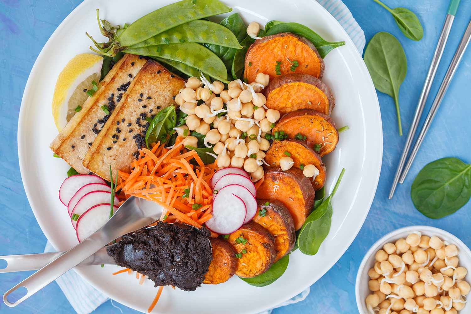 Buddha bowl vegan salad with vegetables, tofu, baked sweet potato, sprouts chickpeas and hemp dressing.