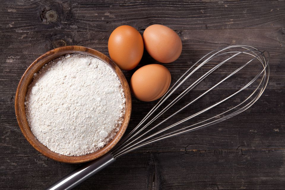 Whisk next to three eggs and a bowl of flour