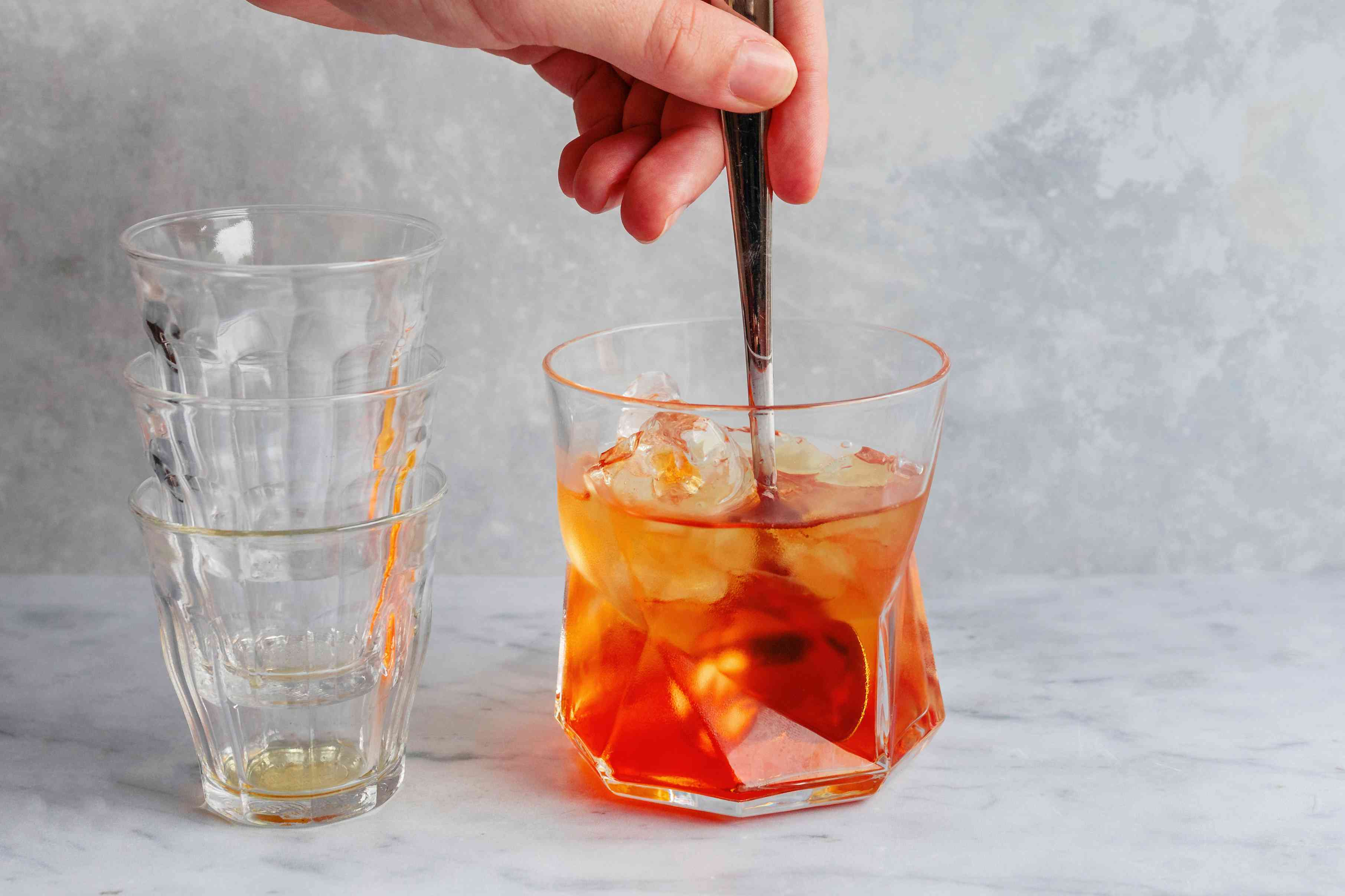 Stir Negroni cocktail in a glass