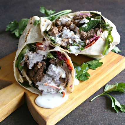 Doner kebab made with lamb and drizzled with tzatziki sauce