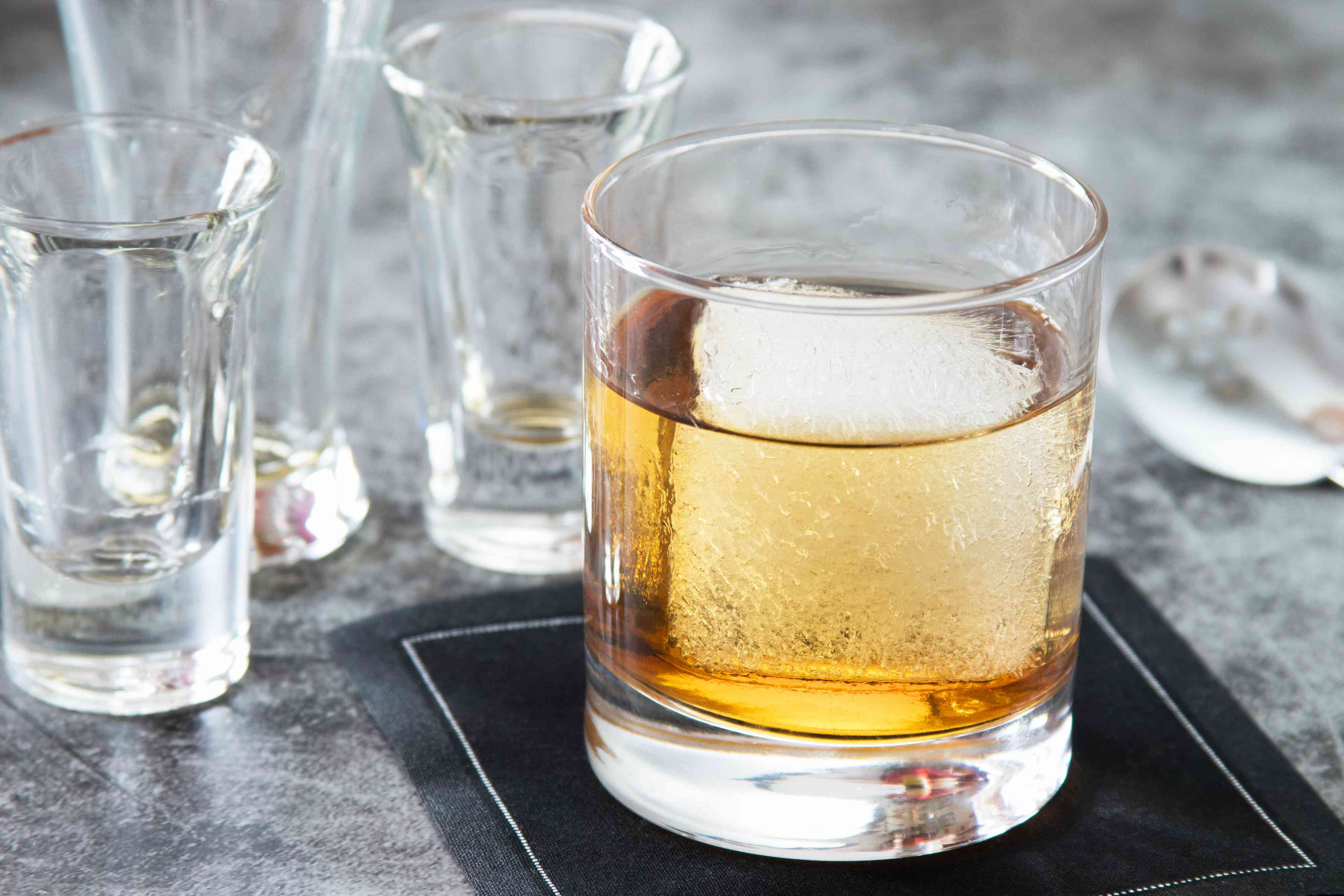Rums and syrup added to a glass with a big ice cube