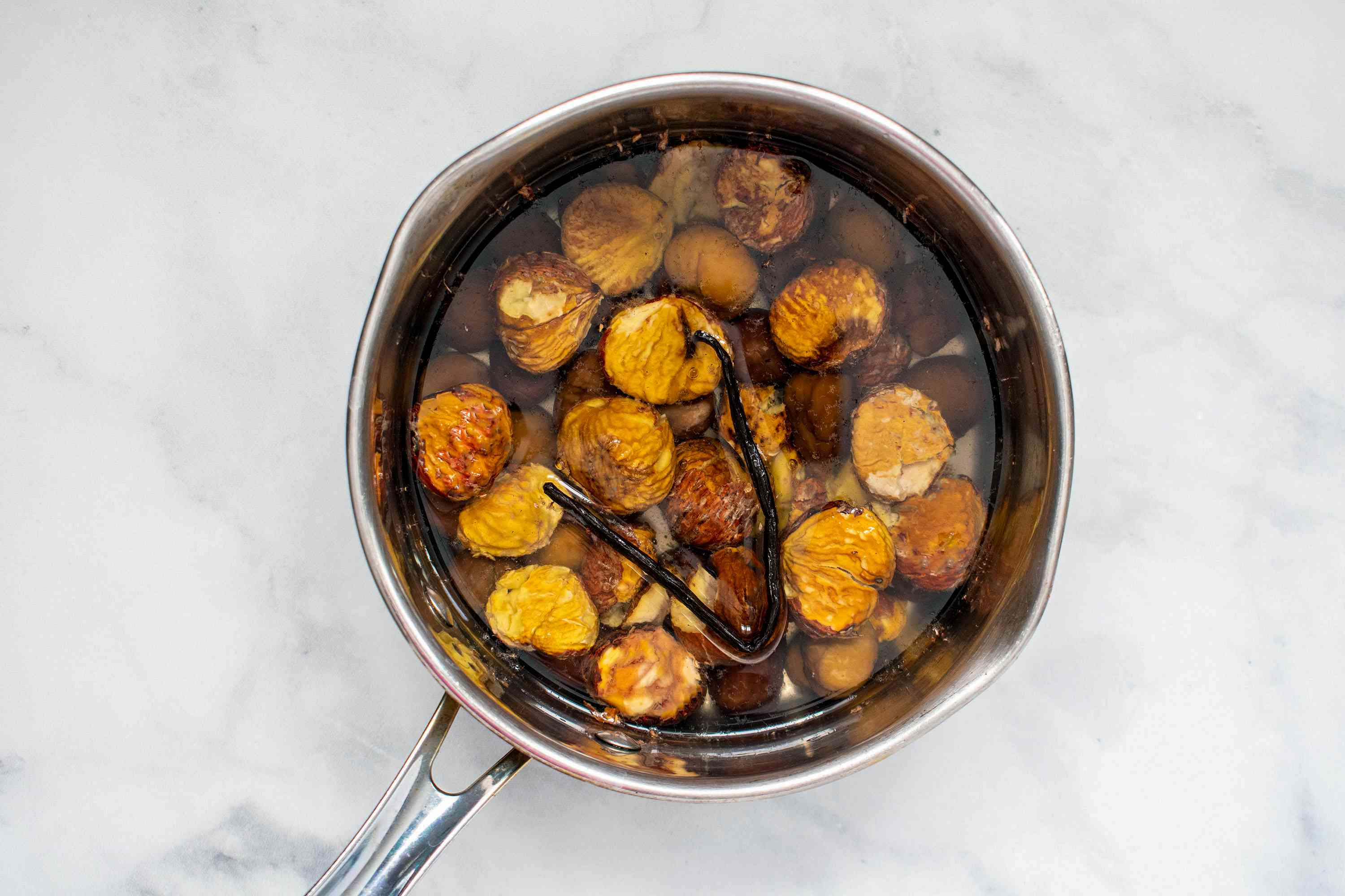 chestnuts with water and vanilla bean in a saucepan