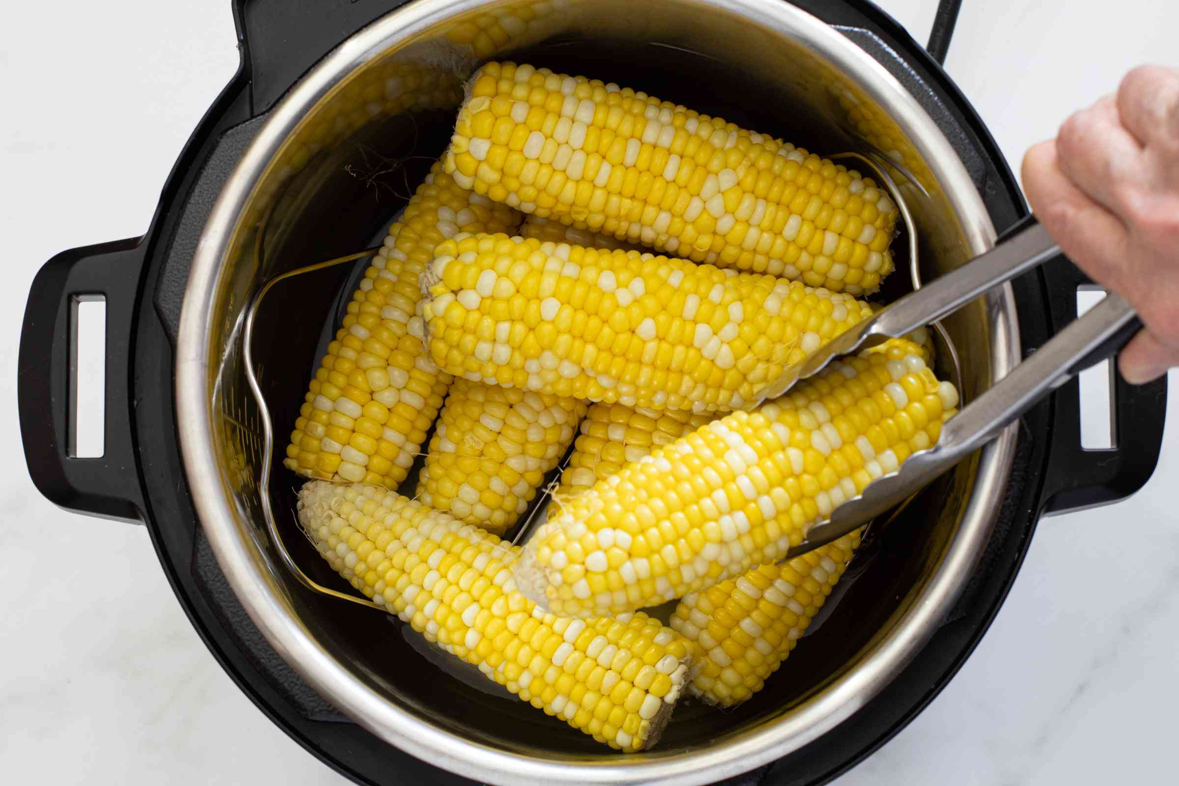Corn on the cob is taken out of the Instant Pot with tongs.