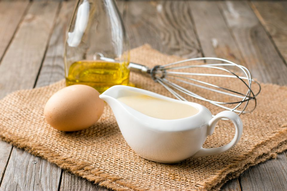 Fresh homemade Mayonnaise with egg, whisk, and bottle of oil on an old wooden table