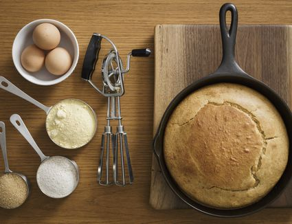 Cornbread in cast iron skillet with ingredients sitting next to it