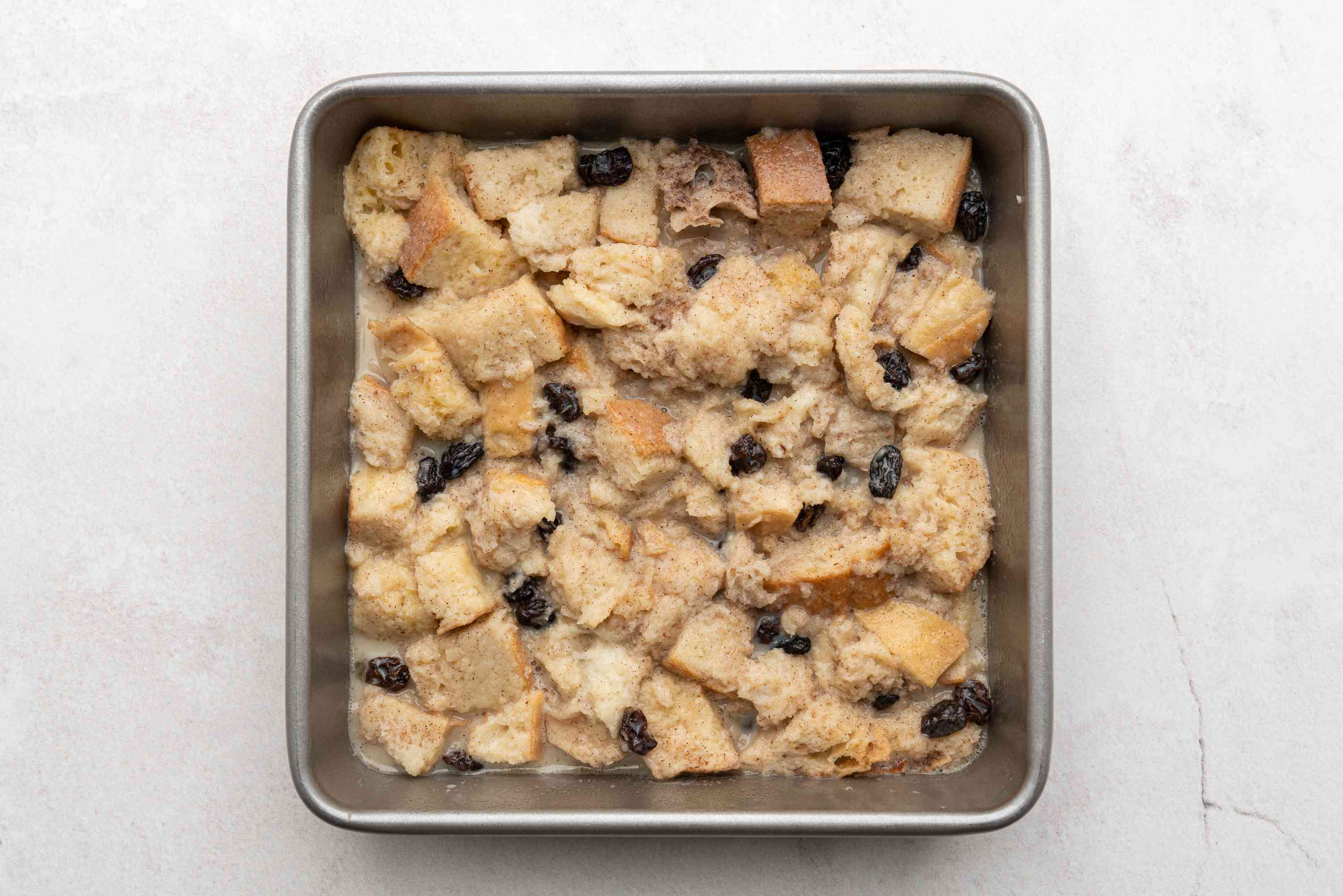 Old Fashioned Spiced Bread Pudding With Raisins mixture in a baking dish