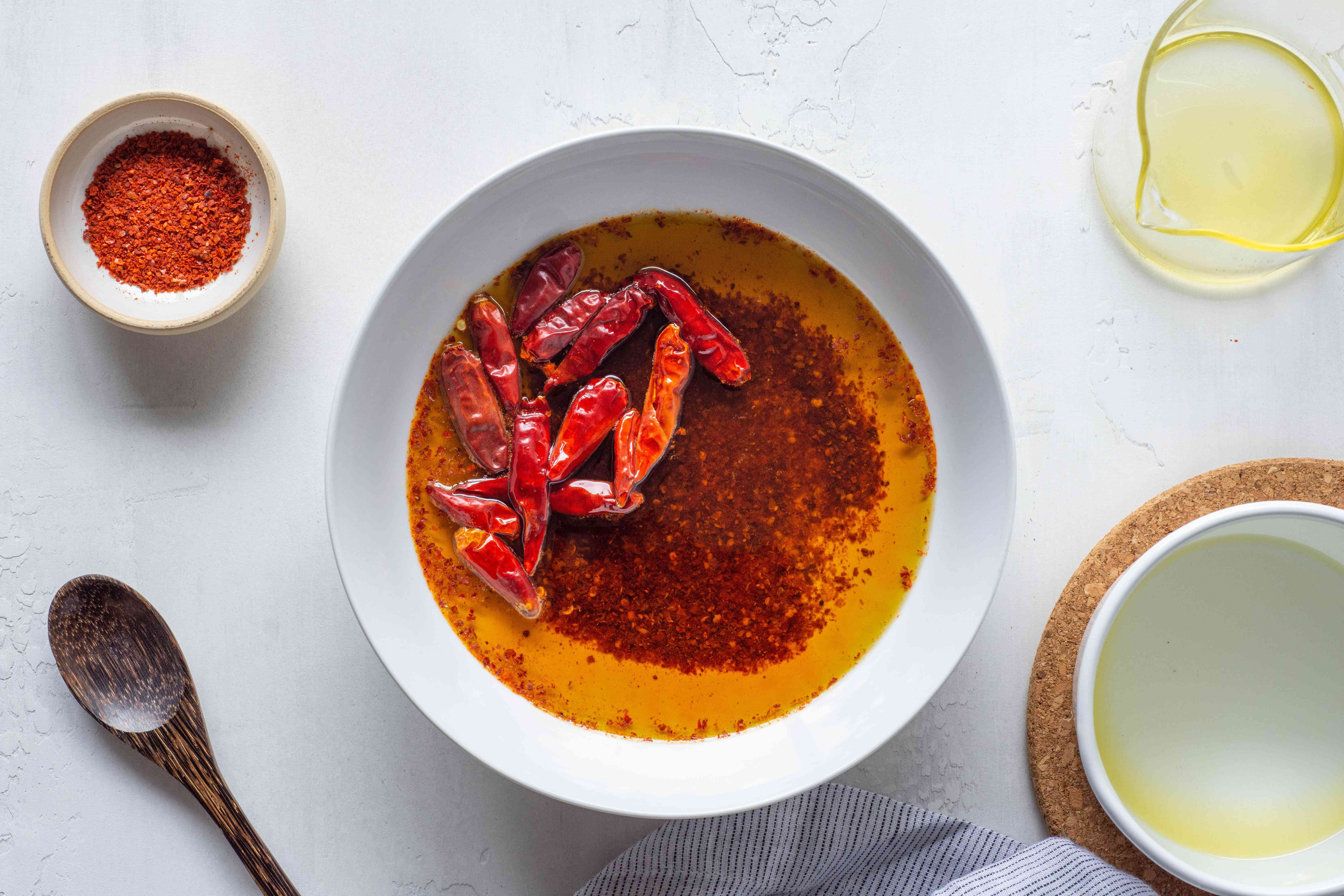olive oil, crushed and whole Chiles in a white bowl