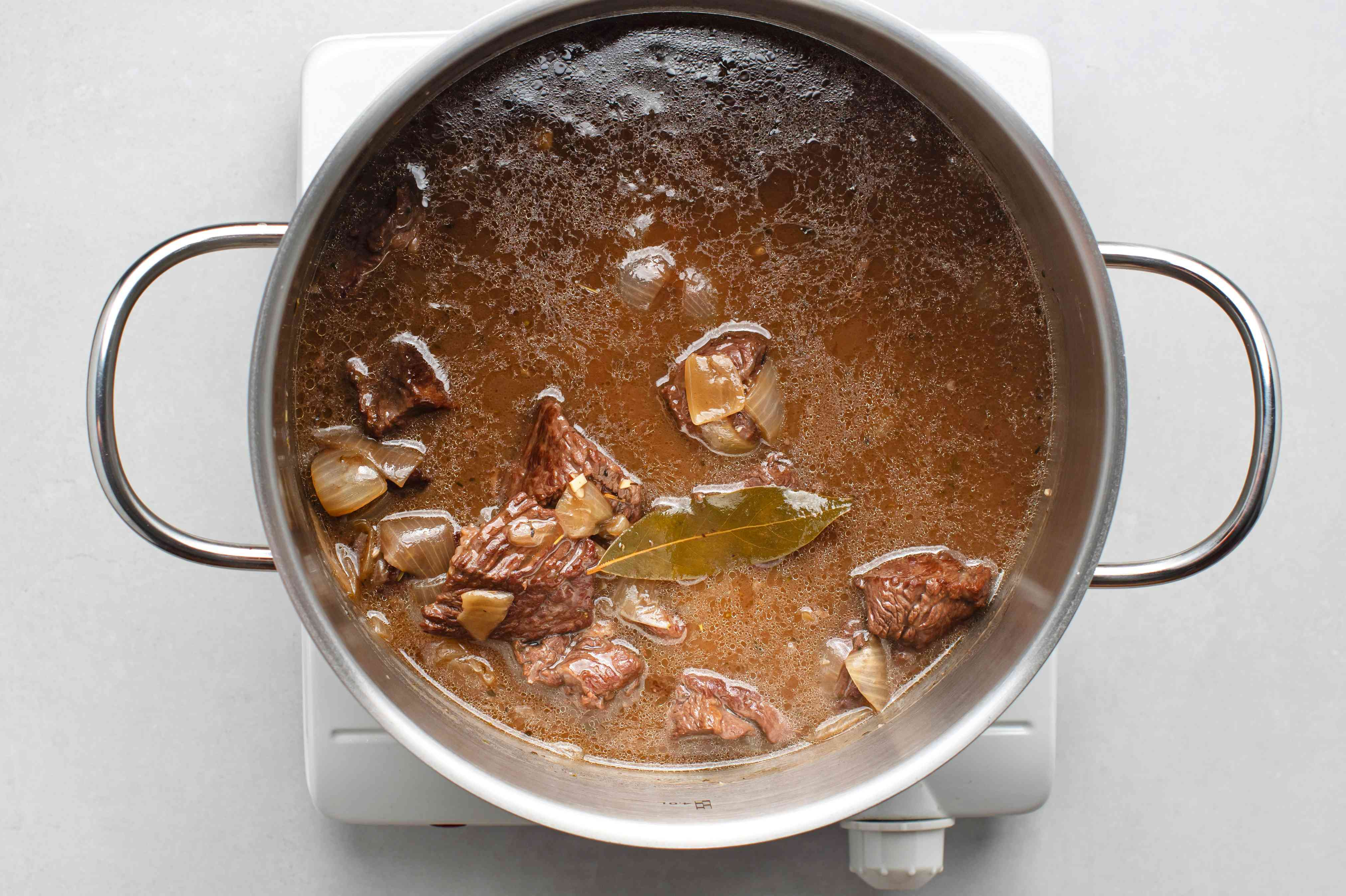 add the broth, beef, thyme, rosemary, and bay leaf to the onion mixture in the pot