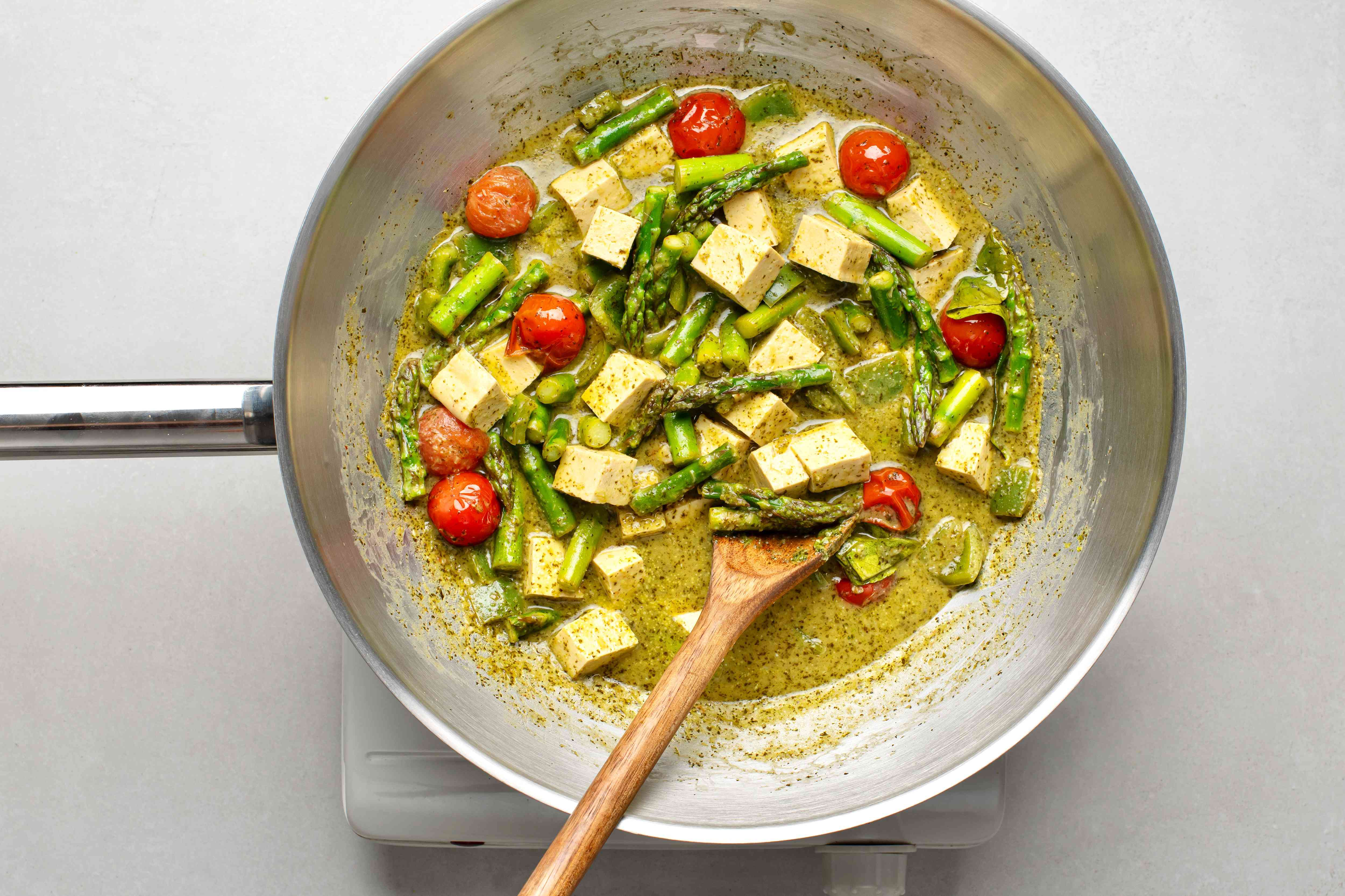 Green curry simmering with coconut milk and veggies added
