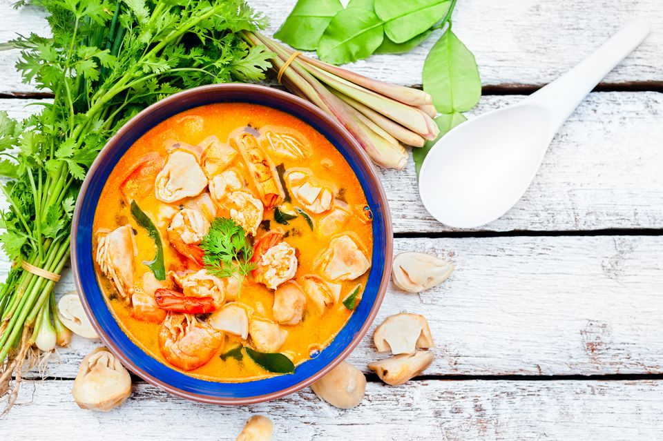 Thai crab curry in blue bowl on wooden table