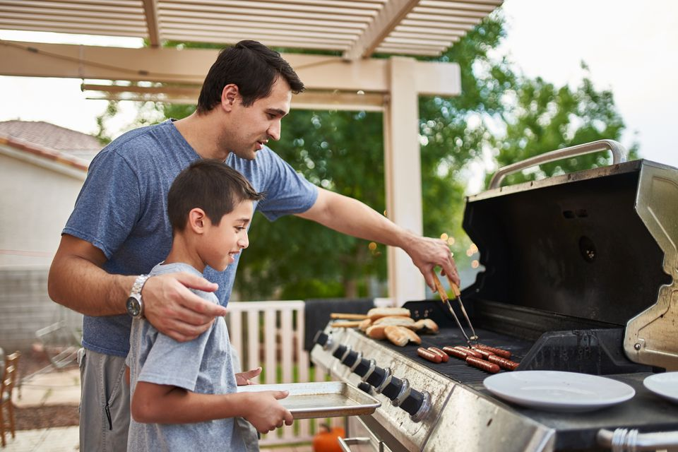 Man teaching son how to grill hot dogs