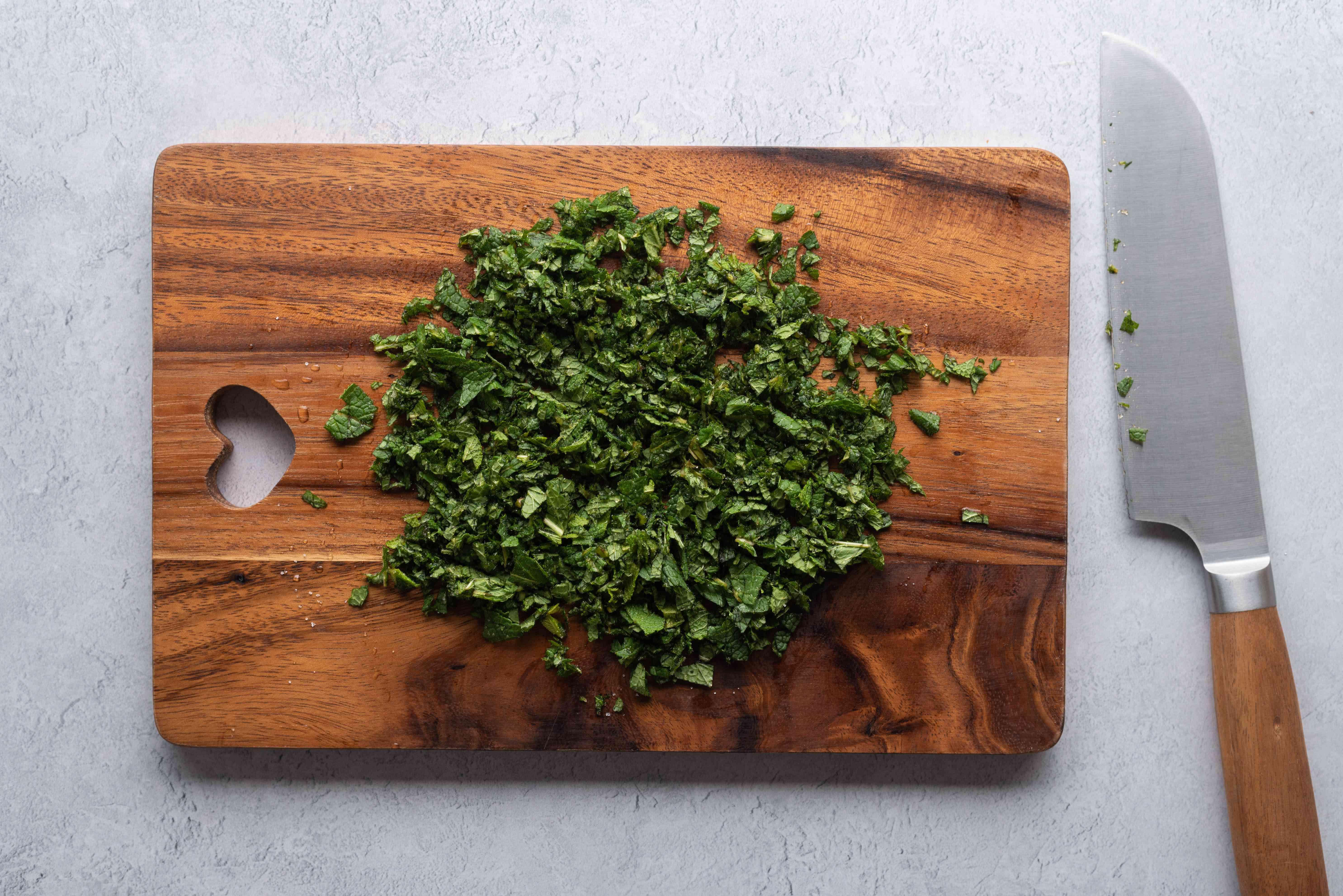 chopped mint leaves on a wood cutting board