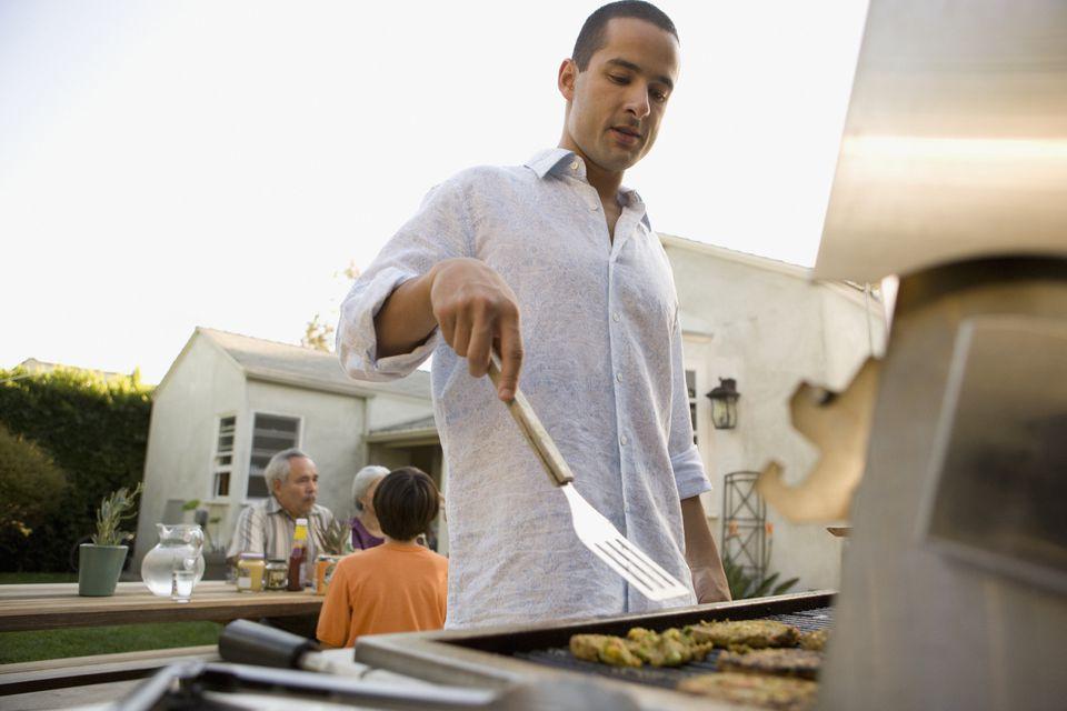 Man grilling in backyard