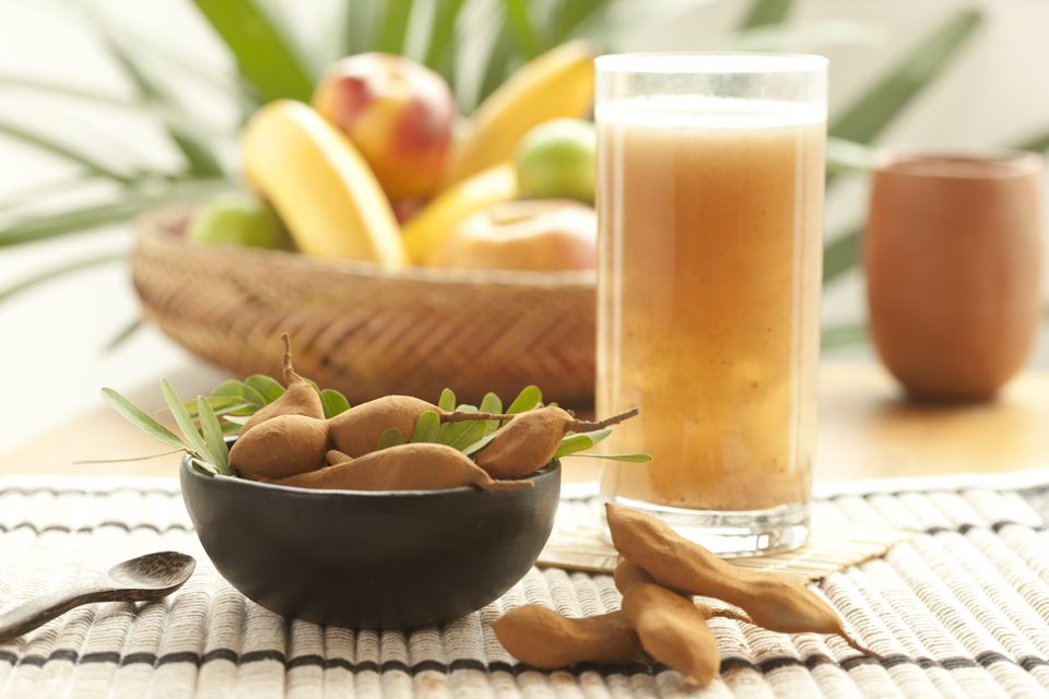 Tamarind fruits in a bowl with a glass of juice