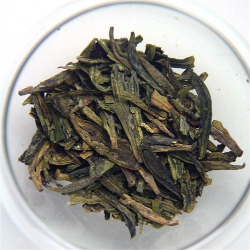 """Long Jing (a.k.a. """"Dragonwell"""" or """"lung Ching"""") green tea from China on a white plate."""