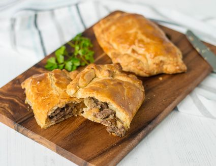 Traditional Cornish beef and vegetable pasty on a wooden cutting board