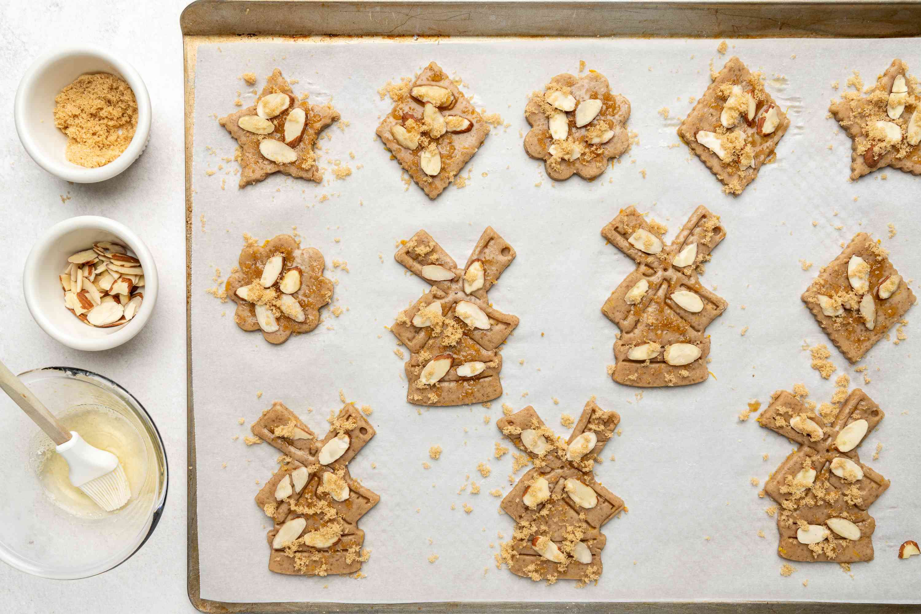 Brush the cookies with egg white and sprinkle brown sugar and flaked almonds on a baking sheet