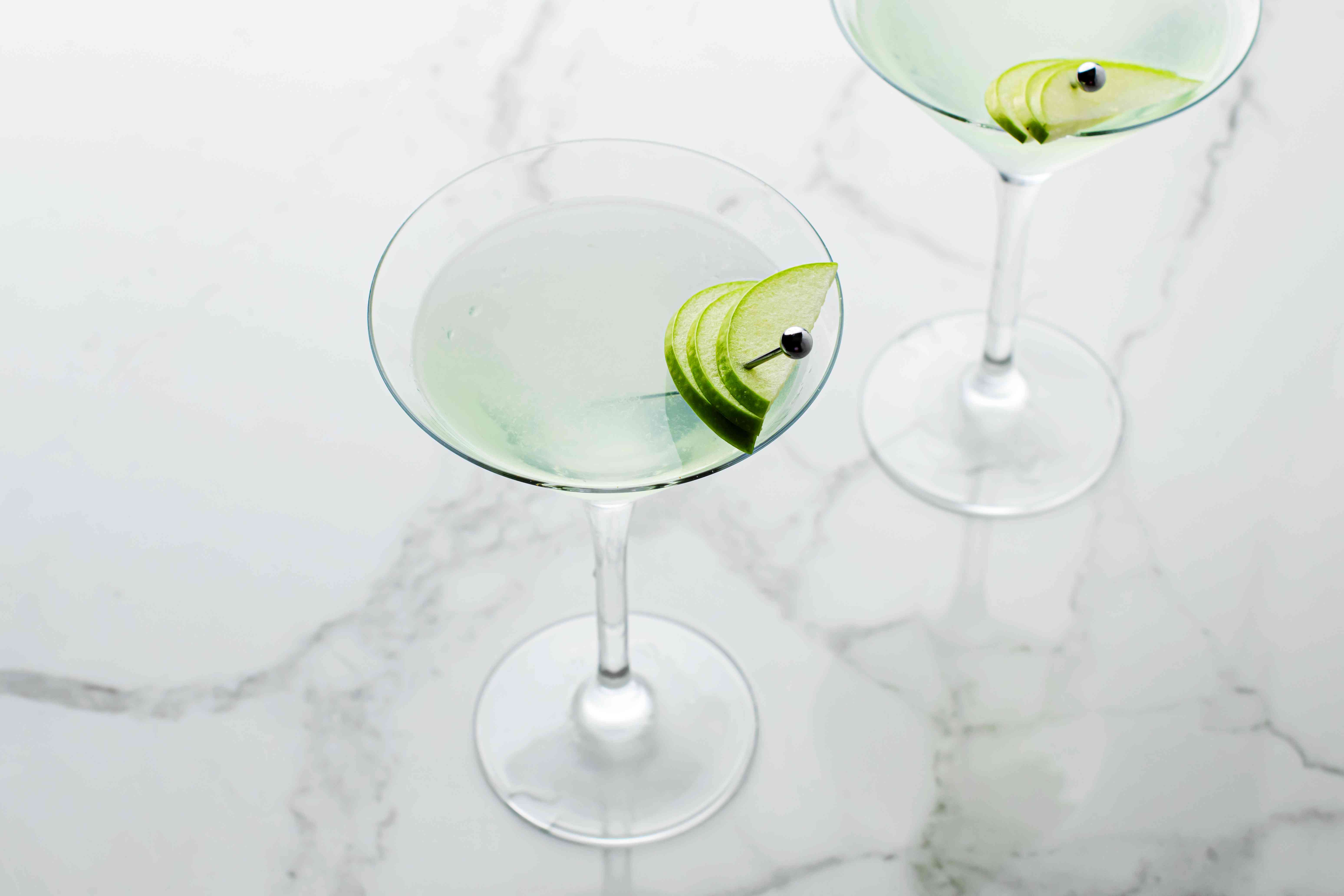 Green apple martini cocktails on a white marble counter
