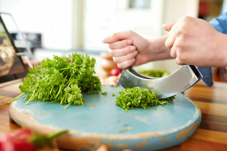 Female hands cutting cilantro with mezzaluna knife