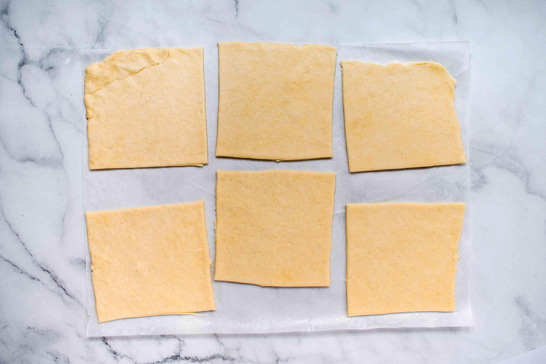 dough cut into squares on parchment paper