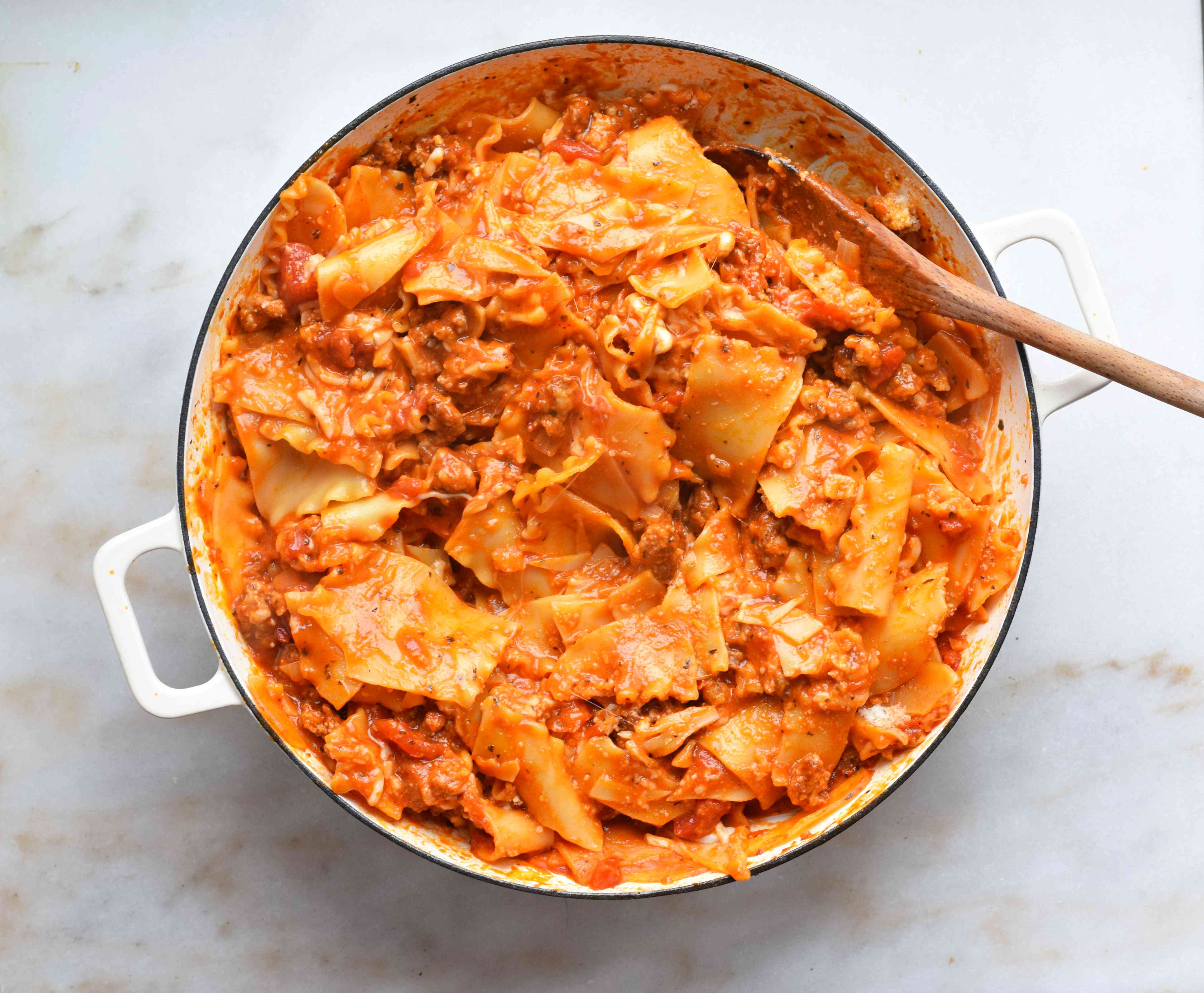 cheese mixed with lasagna noodles and sauce in a skillet