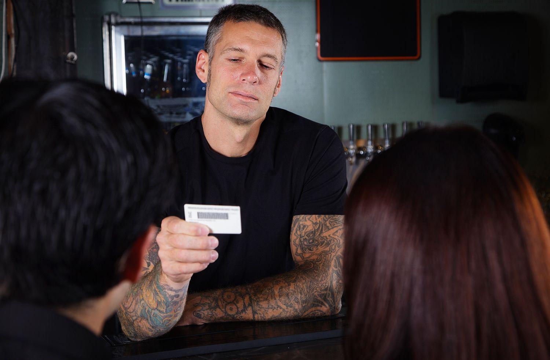A bartender checking IDs